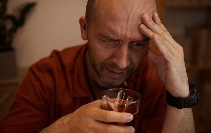 Drunk man holding a glass of alcohol in hands.