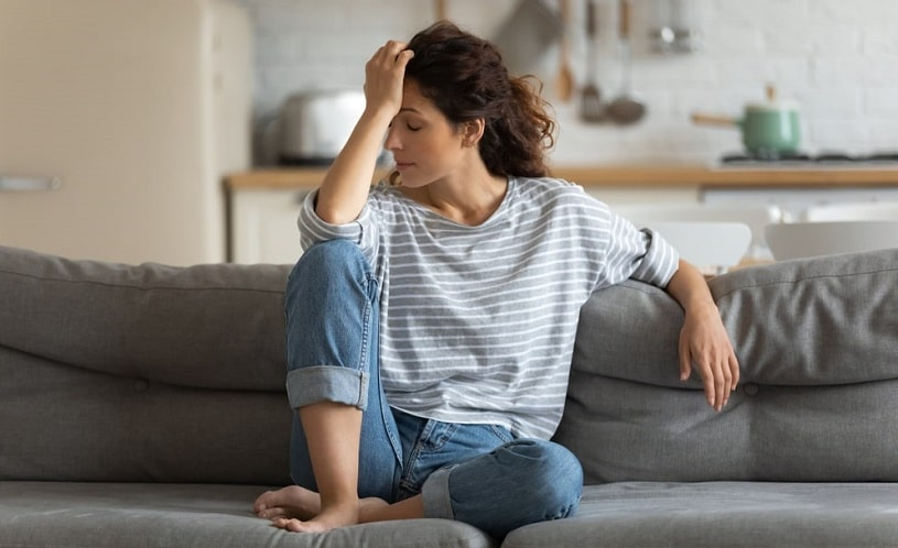 Woman feeling anxiety at home sitting on the couch.