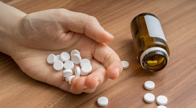 Woman's hand holding many oxycodone pills.