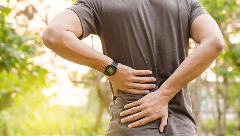 Man experiencing back pain outside.