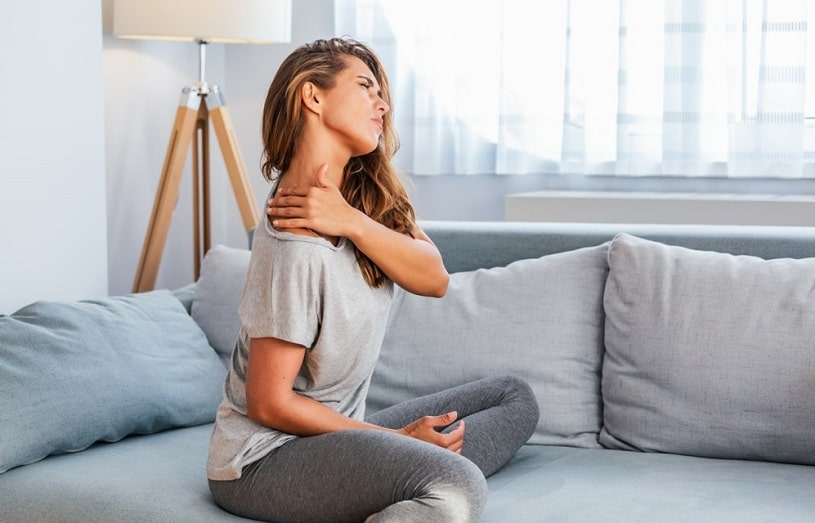 Woman sitting on the couch at home has a pain in her neck.