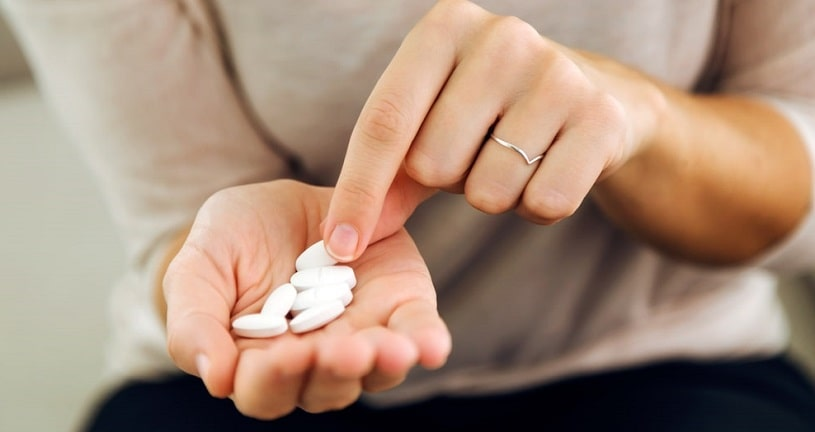 Woman holding pills in her hand, counting them.