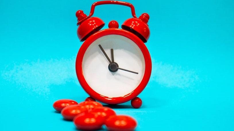 Red pills next to a clock.