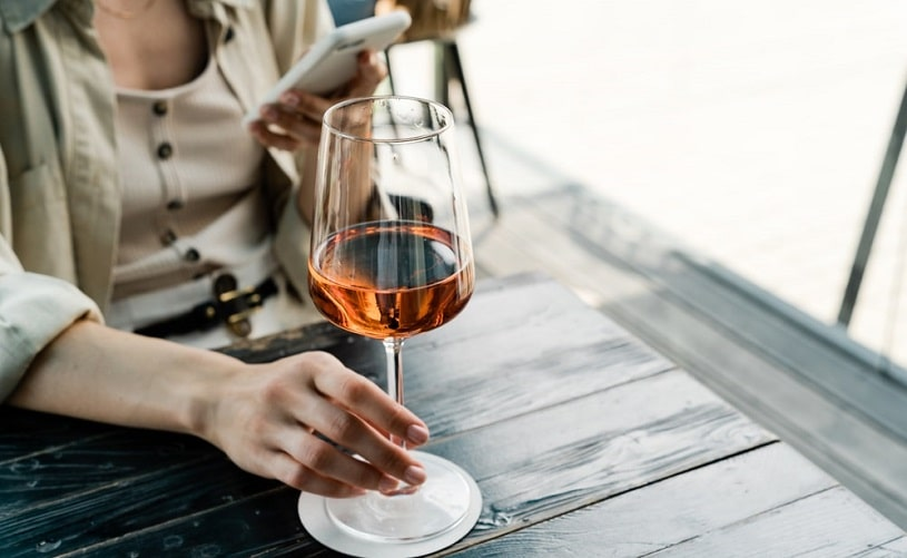Woman drinking a glass of wine at a cafe.