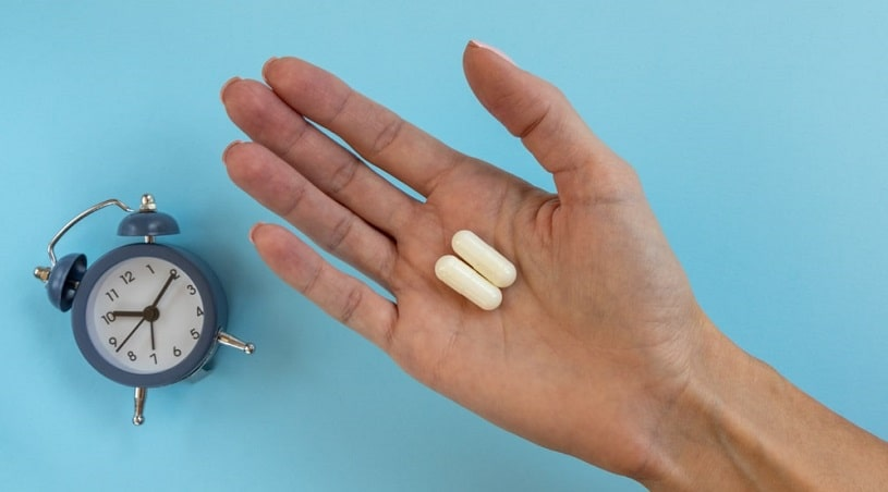 White capsule pills in woman's hands on blue background.