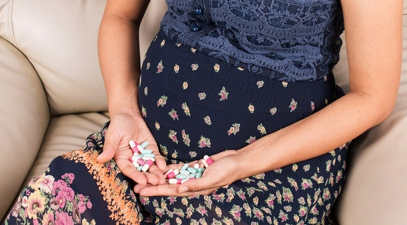 Pregnant woman holding Robaxin vs. Soma pills in hands.