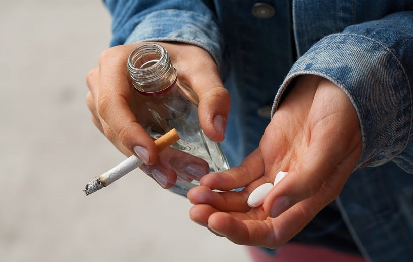 Woman smoking cigarettes and holding pills and vodka in her hands.
