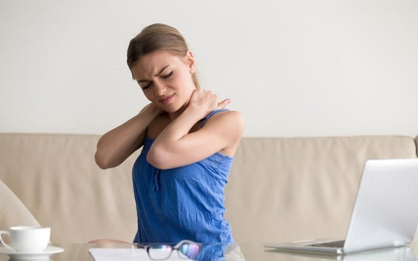Woman feeling neck pain massaging her back.