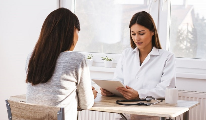 Young female doctor talking to a patient about Librium addictive potential.