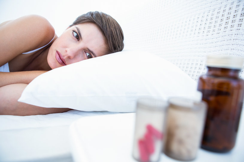 A disappointed woman in bed looks at pills on the table.