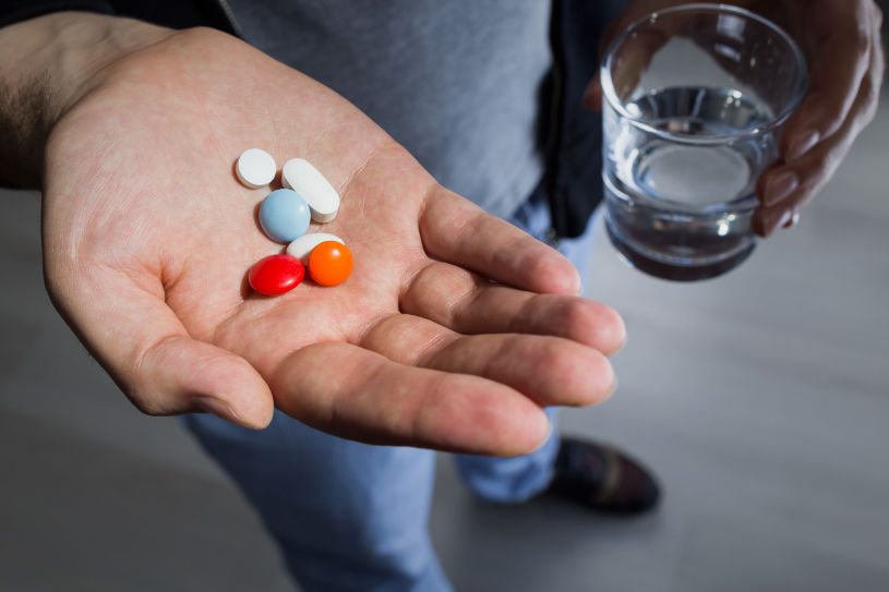 A man holds pills and a glass of water.