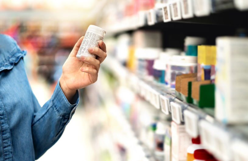 A woman holds a bottle of pills in the pharmacy.