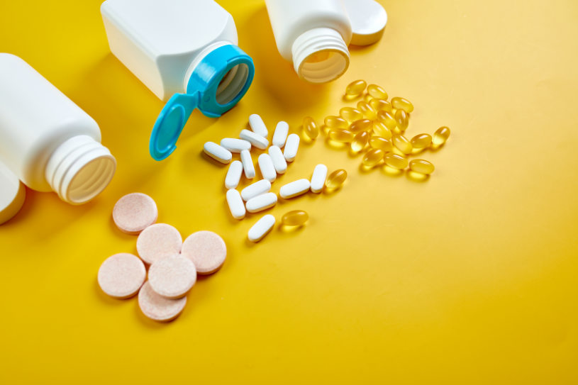 Different pills and capsules are on the yellow background.