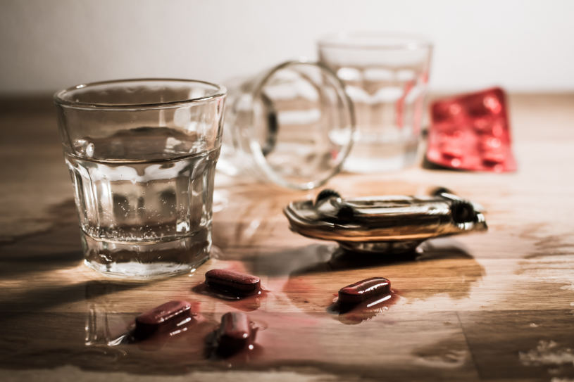 Pills and a glass of alcohol on the table.