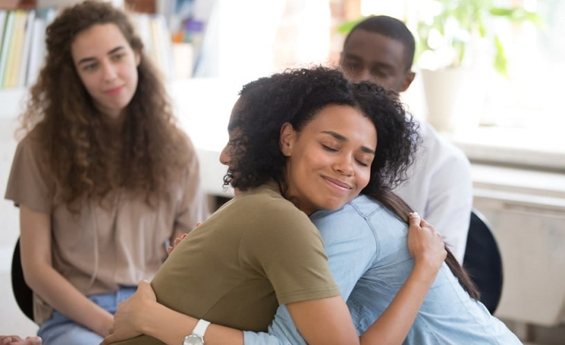 People hugging at a support group meeting.