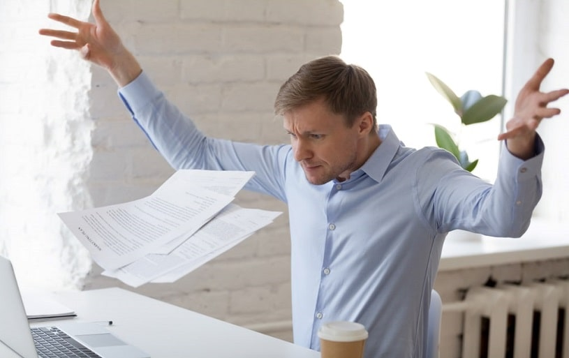 Angry man sitting at workplace throws documents.