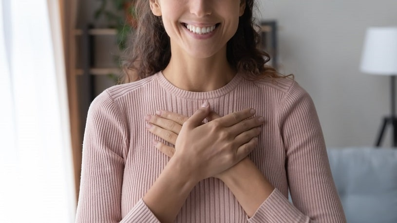Calm and delighted woman holding folded hands on chest.