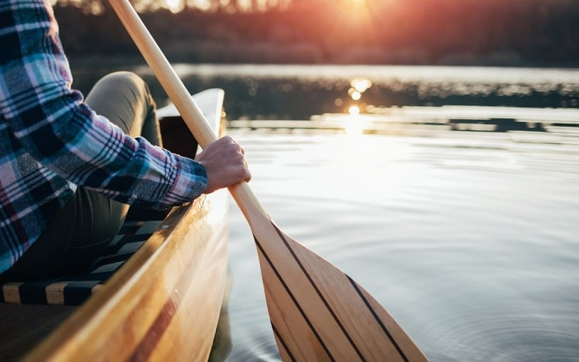 Close up of a girl paddling a canoe.