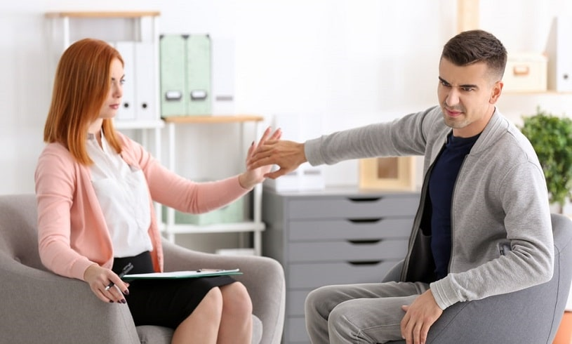 Drug addict refusing rehab treatment while talking to a therapist.