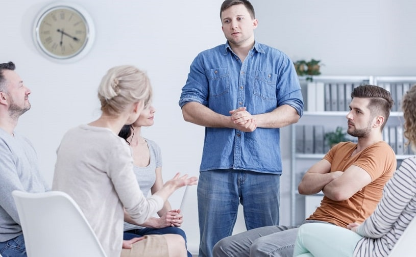 Close people conducting a drug intervention with a young man.
