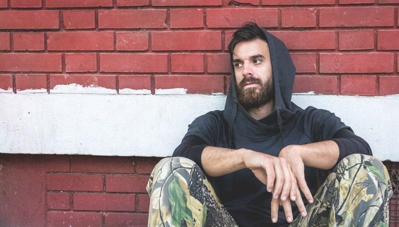 Addicted depressed man sitting on the street.