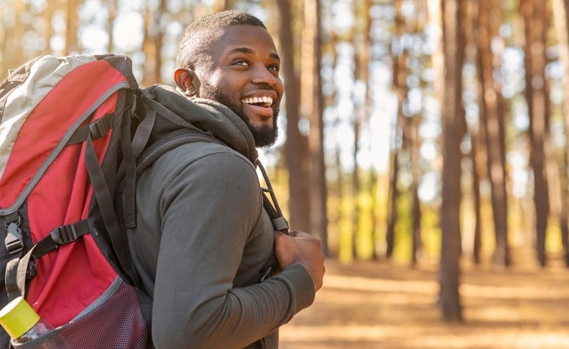 Man with backpack smiling during adventure therapy hiking.