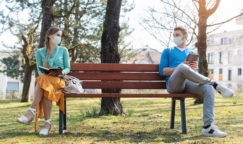 Social distancing: man and woman wearing masks on the benach in the park.
