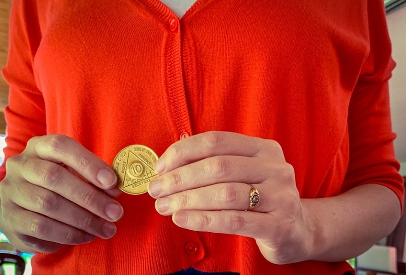 Woman holding AA 10-month sobriety chip.