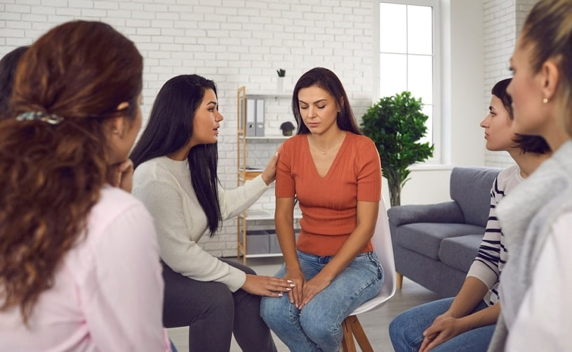 Women supporting each other at a Women for Sobriety meeting.