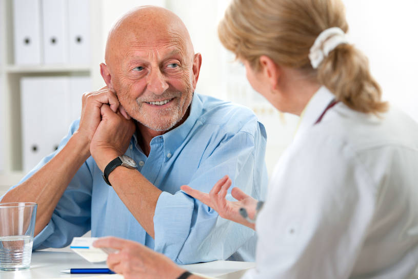 Doctor talking to senior patient. at rehab
