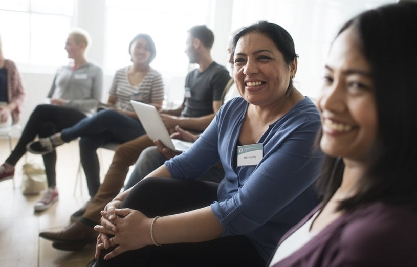 Group of people sitting indoors smiling and communicating.