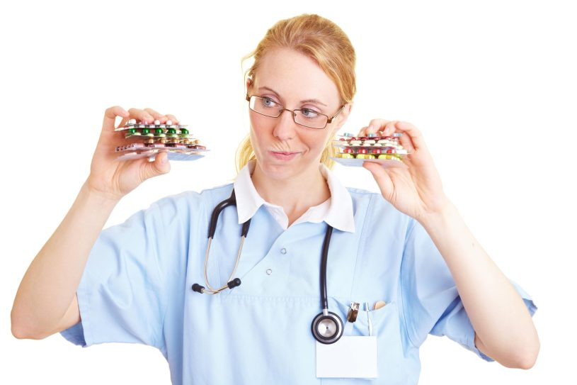 Nurse is holding many colorful pills