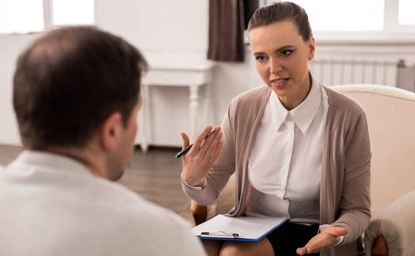 Therapist explains something to a patient at a motivational interviewing session.