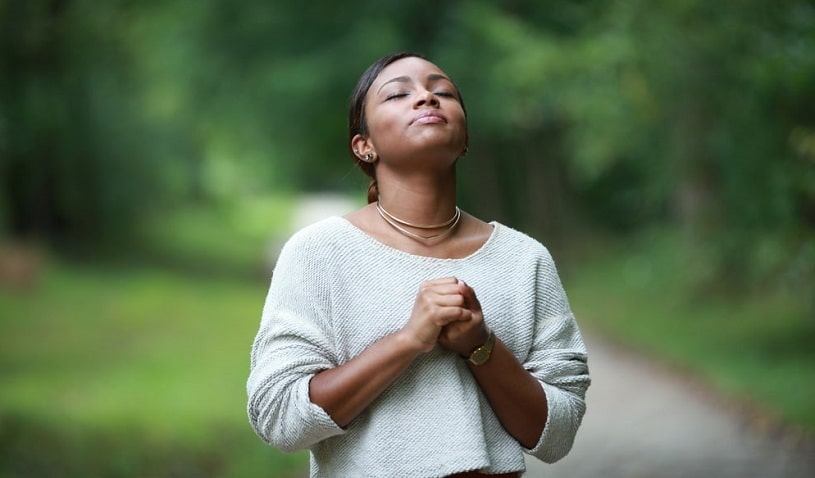Woman praying hoping that higher power will help her.