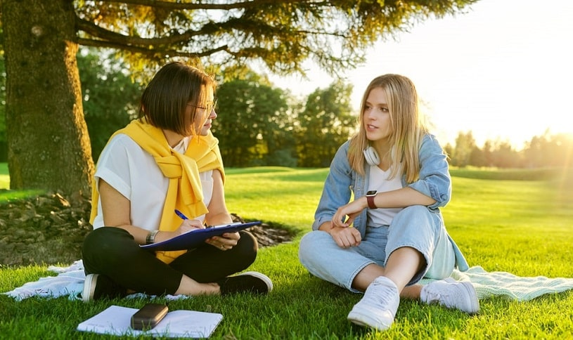 Therapist and patient discussing something outdoors in the park.