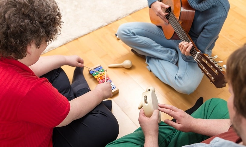 Three people playing musical instruments together.
