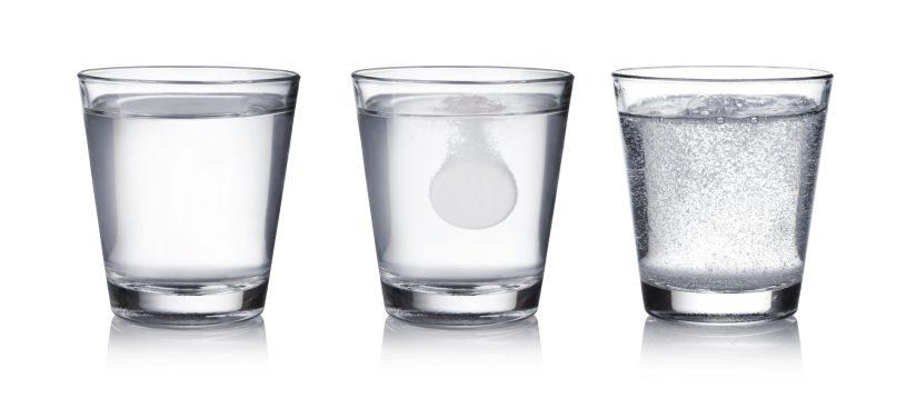 White pill dissolving in the glass