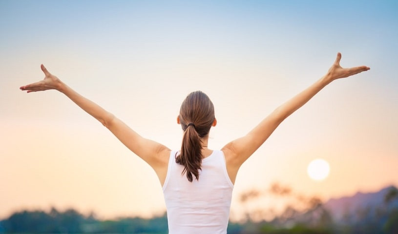 Happy confident woman raising her arms.